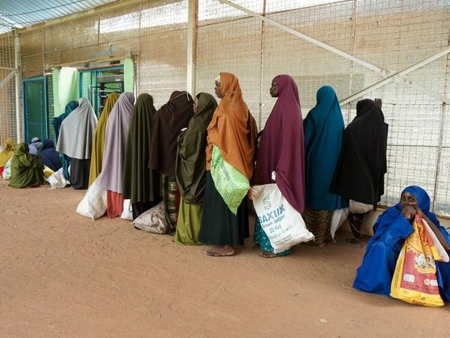 Frauen in bunten Kleidern und Kopftüchern bilden im Lager Dadaab in Kenia eine Schlange vor der Essensausgabe der WFP.