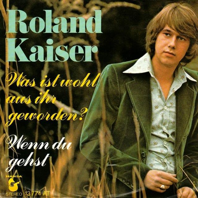 Junger Roland Kaiser lehnt an Baum.