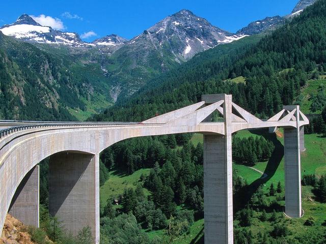 Eine Brücke in grüner Berglandschaft.