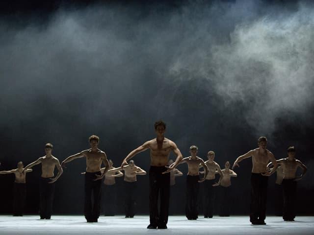 Zehn Tänzer mit nackten Oberkörpern, über ihnen Rauch.
