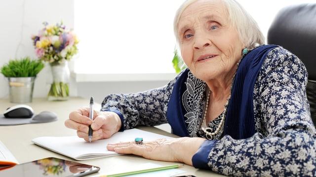 Alte Frau schreibt Brief.