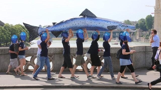 Menschen mit Fischhüten tragen Lachs-Modell