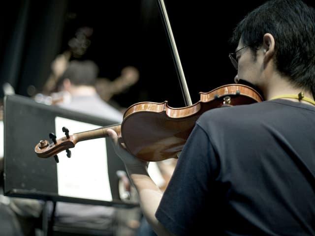 Rückensicht auf einen jungen Mann, der vor einem Notenständer sitzt und Geige spielt.