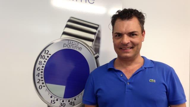 Andreas Mossner, der Erfinder der Züri-Uhr vor einem Plakat mit seiner Erfindung.