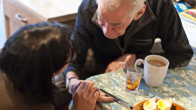 Ein alter Mann sitzt am Tisch mit einer Betreuerin