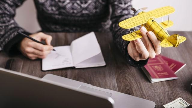 Ein Mann sitzt vor einem Computer und hält ein gelbes Holzflugzeug in der Hand.