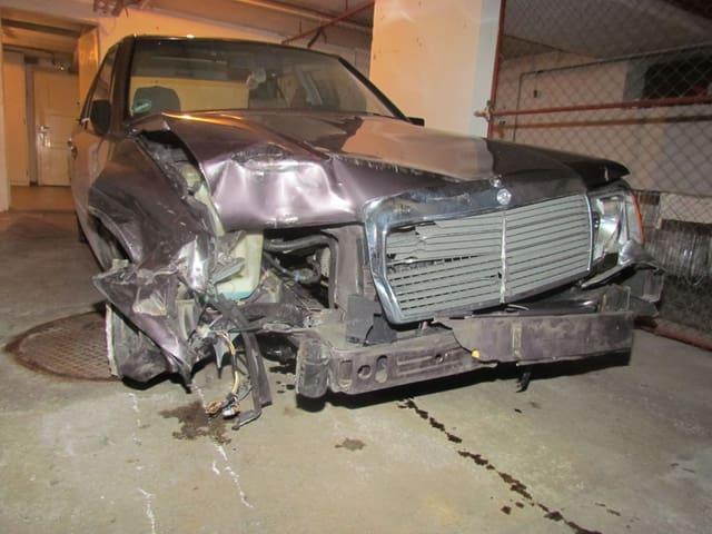 Der stark zerstörte Mercedes in einer Garage, davor eine Ölspur.