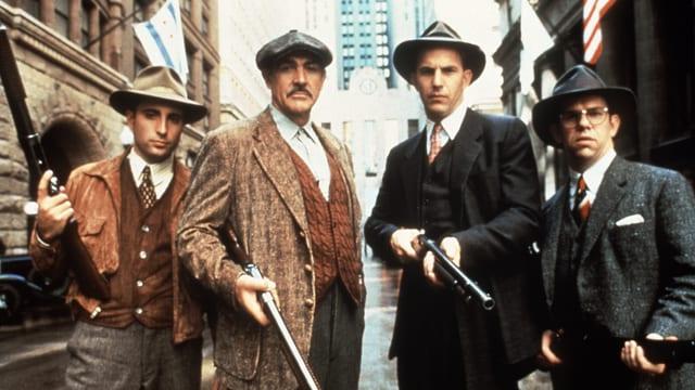 Vier Männer mit Gewehren und unheilvollem Blick.
