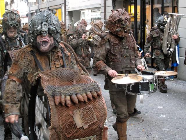 Musizierende Fasnächtler. Ihre Kostüme sehen aus wie rostige Rüstungen.