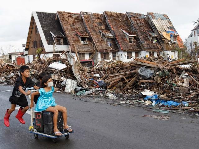 Ein Kind schiebt ein anderes auf einem Wagen mit zwei Kanistern vor einem grossen Trümmerfeld hindurch.