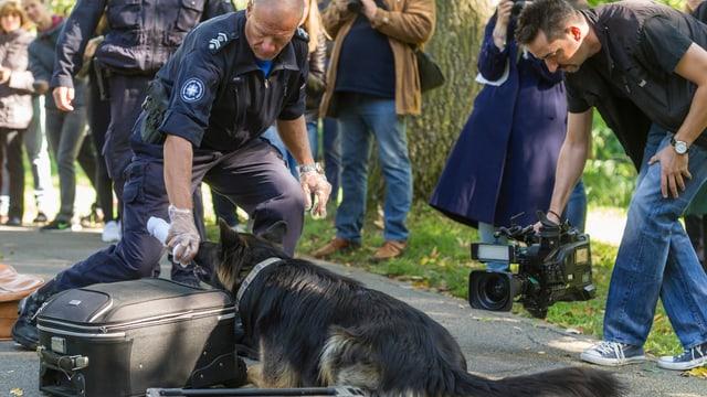Grenzwächter durchsucht mit einem Spürhund verdächtige Gepäckstücke im Zoo Basel