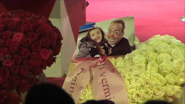 Ein Blumenkranz mit einem Foto von Chanel Knie und Spidi