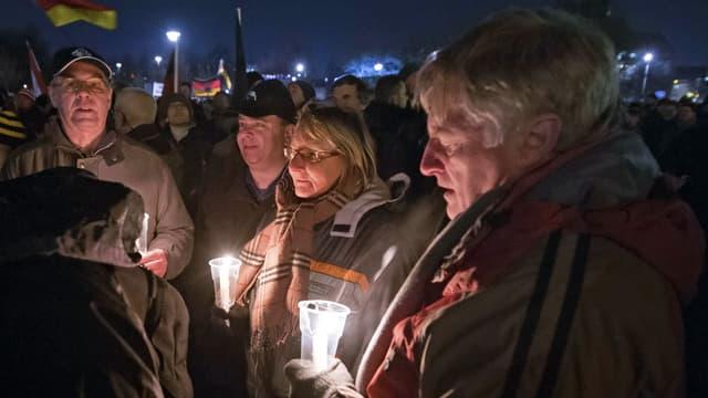 Aufnahme der Demonstranten, mehrere ältere Frauen und Männer stehen herum, sie halten brennende Kerzen.