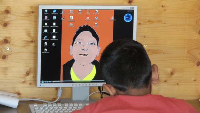 Ein Asylsuchender vor einem Computer.