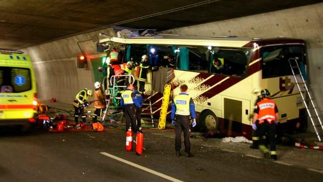 Bus destruì en in tunnel, persunas da salvament èn enturn il bus. Sper il bus è in'ambulanza.
