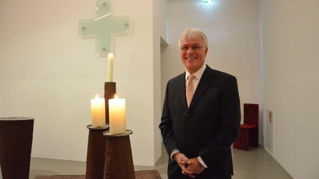 Eugen Eckert mit weissem Haar und in dunklem Anzug steht in der Stadionkapelle neben drei Kerzen.