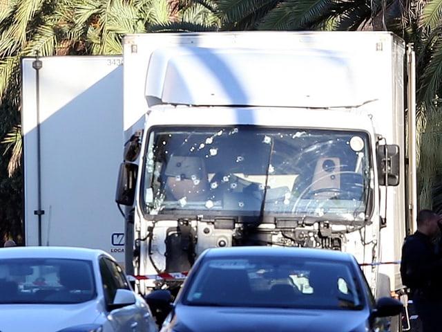 Weisser Lastwagen mit Einschusslöchern auf der Windschutzscheibe.