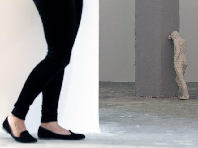 Dei Beine einer Frau stehen vor einer Skulptur, die an einem Pfeiler lehnt.