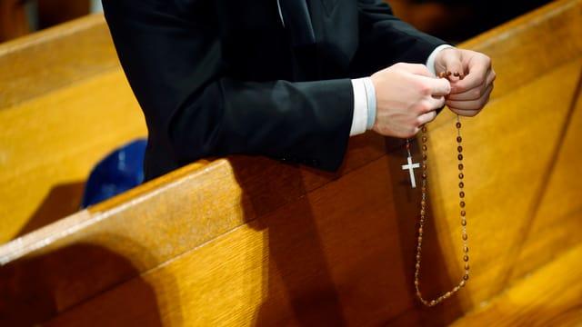 Kleriker hält Rosenkranz in Hand und betet.