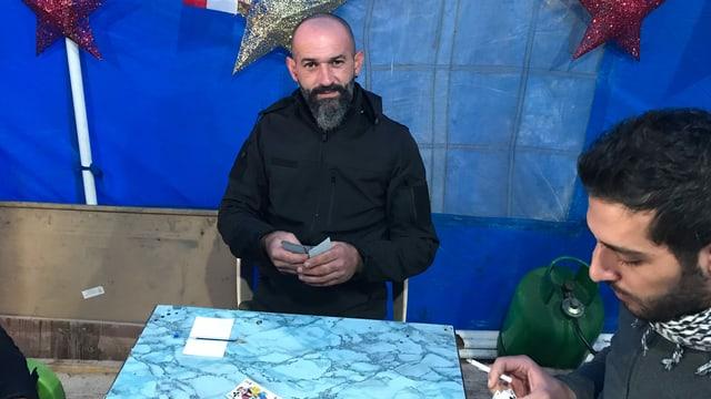 Mann, der an einem Tisch mit anderen Männern sitzt. Er hält Karten in der Hand.
