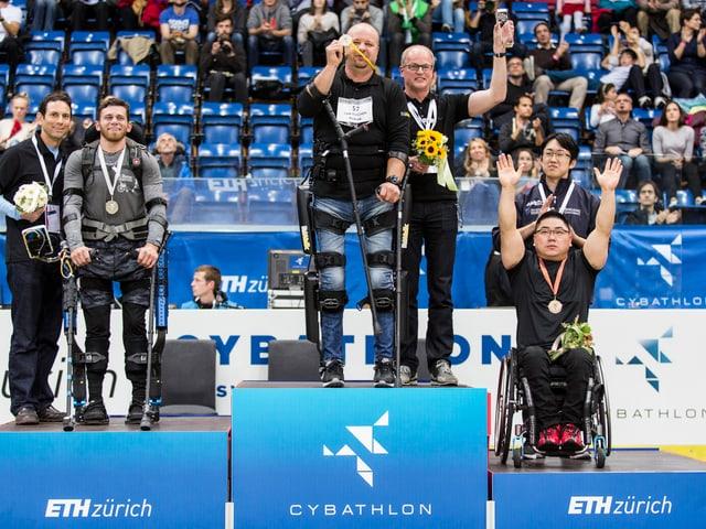 Drei Teilnehmer, gestützt von Eko-Skeletten, an der Siegerehrung.