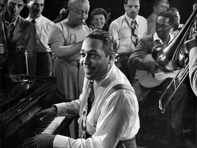 Pianist Duke Ellington sitzt am Klavier umgeben von Mitmusikern.