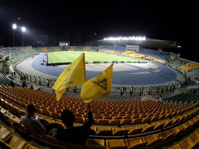 Zwei Fans sitzen auf den Tribünen im Stadion.
