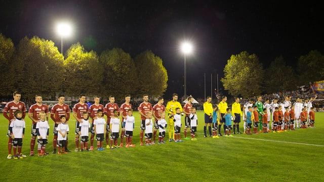 Die beiden Mannschaften vor dem Anpfiff - am Spielfeldrand grosse Bäume.