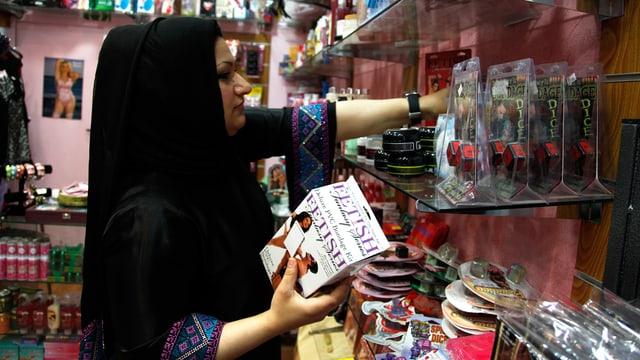 Eine muslimische Verkäuferin eines Sexshop räumt ein Regal ein.