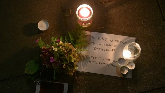 """Blumen und Kerzen und ein Zettel mit dem Titel """"Für eine offene Gesellschaft"""" liegen Nahe der Hamburgert Synagoge am Boden"""