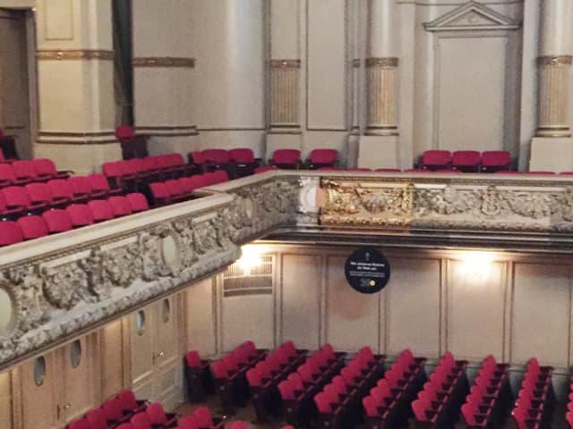 Eine Tribüne mit roten Stühlen. Die Verzierung an der Tribüne ist an einer Stelle ganz golden, sonst schal weiss.