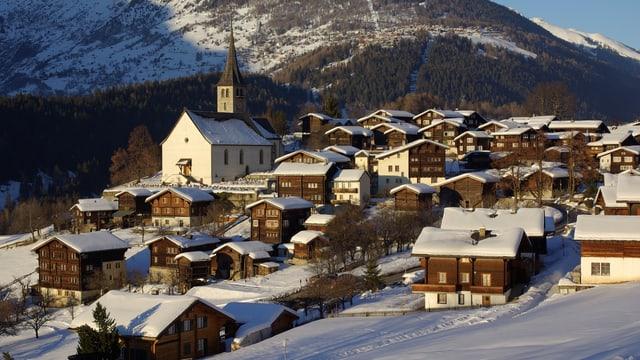 Verschneites Dorf mit Dorfkirche in der Mitte.