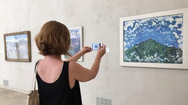 Frau fotografiert mit dem Smartphone ein Bild.