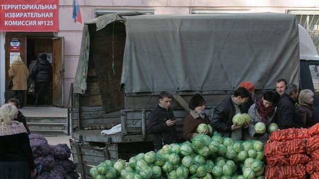 Menschen bei Gemüsekörben hinter einem Armee-Lastwagen