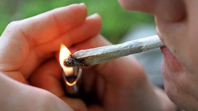 Ein Mann zündet einen Joint an
