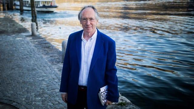 Der britische Schriftsteller Ian McEwan steht mit einem Buch unter dem Arm am Ufer eines Flusses.