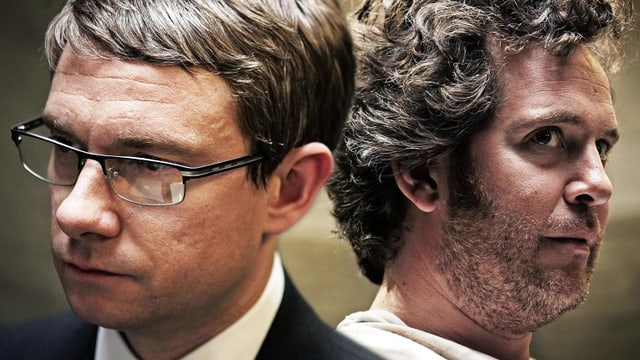 Zwei Männer sind Rücken an rücken. Der eine trägt eine Brille.