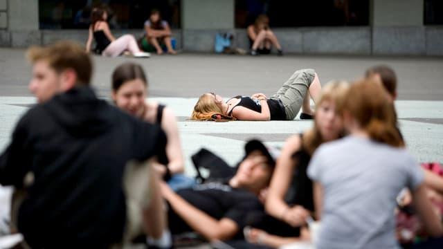 Jugendliche liegen und sitzen auf einem Platz herum.