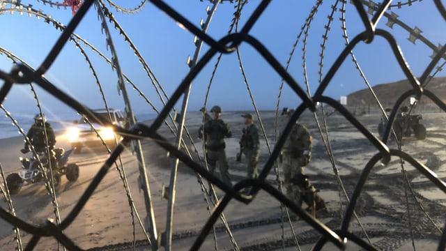 US-Soldaten überprüfen einen Migranten, fotografiert durch einen Maschendrahtzaun.