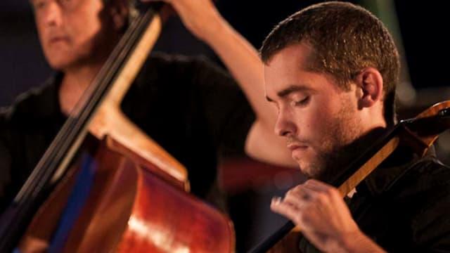 Ein Cellist im Vordergrund, ein Bassist im Hintergrund.