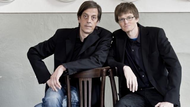 Zwei Männer sitzen auf Stühlen