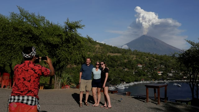 Touristen posieren vor Vulkan. Guide schiesst ein Foto.
