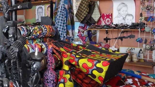 Geschnitzte Figuren, bunte Taschen und Tücher, Armreifen und Zeichnungen in Mapendos Boutique