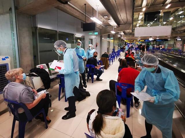 Flughafen in Bangkok. Alle in Schutzkleidung