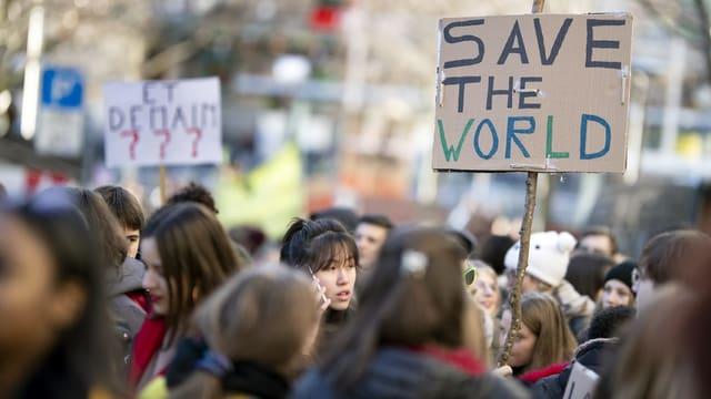 Gruppe von Jugendlichen. Auf einem Plakat steht: Save the World.