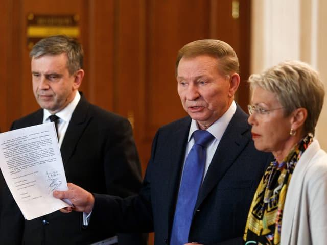 Russlands Botschafter in der Ukraine, Michail Surabow, der frühere ukrainische Präsident Leonid Kuchma und die Schweizer Diplomatin Heidi Tagliavini treten vor die Medien.