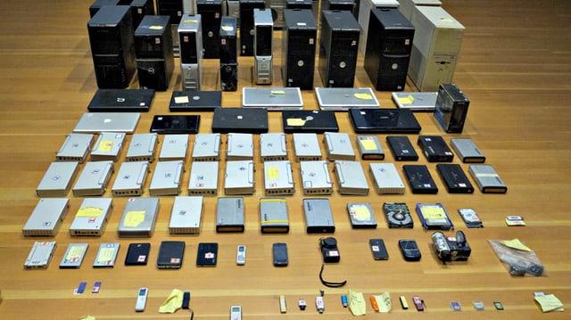 Auf dem Boden sind verschiedene elektronische Geräte - vom Computer über Festplatten bis zu USB-Sticks säuberlich nach Grösse angeordnet.