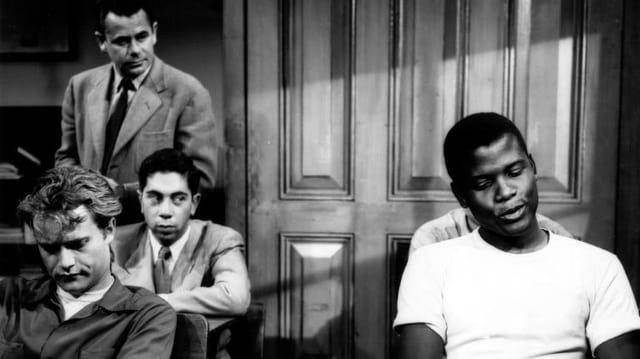 Das schwarzweiss Bild zeigt eine Szene im Klassenzimmer aus dem Film. Links hinten steht Glenn Ford, der den Lehrer Richard Dadier spielt. Die Schüler sitzen auf ihren Plätzen. Drei von ihnen sind auf dem Bild zu sehen.