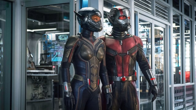 Ein Labor, im Hintergrund Computer. Im Vordergrund stehen zwei Menschen in engen Anzügen und mit Helmen, die ihre Gesichter verdecken.