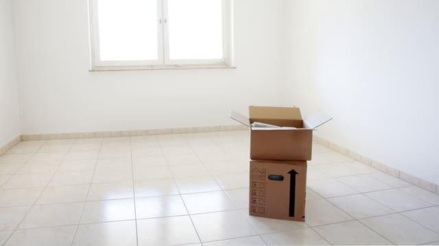 Eine leerer Wohnraum – bis auf zwei Kartonschachteln.